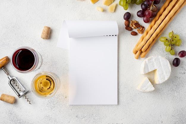 Cuaderno al lado de vino y queso para degustar