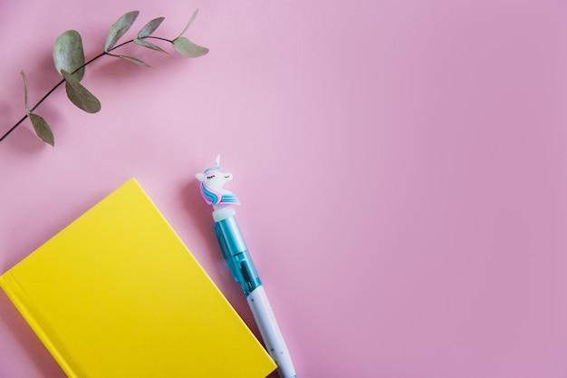 Cuaderno amarillo para notas, gracioso bolígrafo de unicornio y hojas de eucalipto verde sobre fondo rosa pastel. endecha plana. vista superior. copia espacio