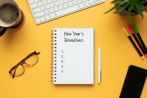 Cuaderno de año nuevo 2020 con lista de resoluciones y objetos sobre fondo amarillo