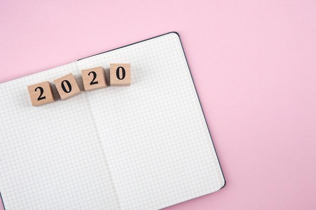 Cuaderno de año nuevo 2020 sobre fondo rosa