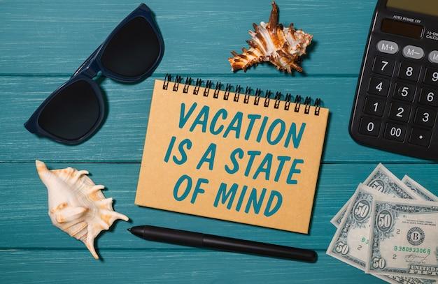 Cuaderno artesanal con las palabras lets travel again, gafas, dinero, calculadora y conchas marinas