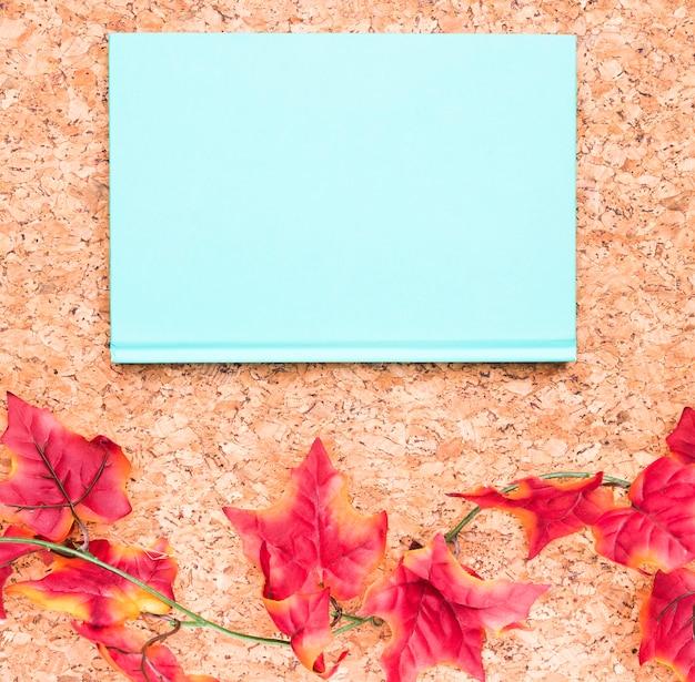 Cuaderno azul y hojas de arce.