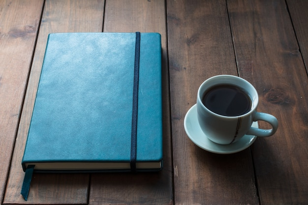 Cuaderno azul con taza de café sobre fondo de madera