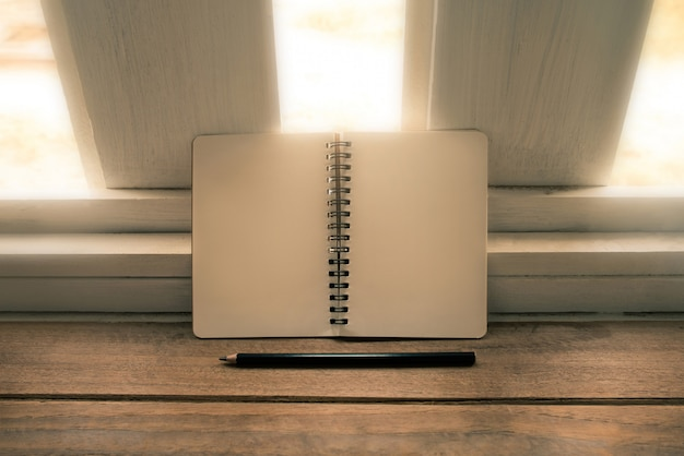 Cuaderno de banco y lápiz sobre mesa de madera tono vintage