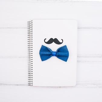 Cuaderno con bigote decorativo y pajarita.