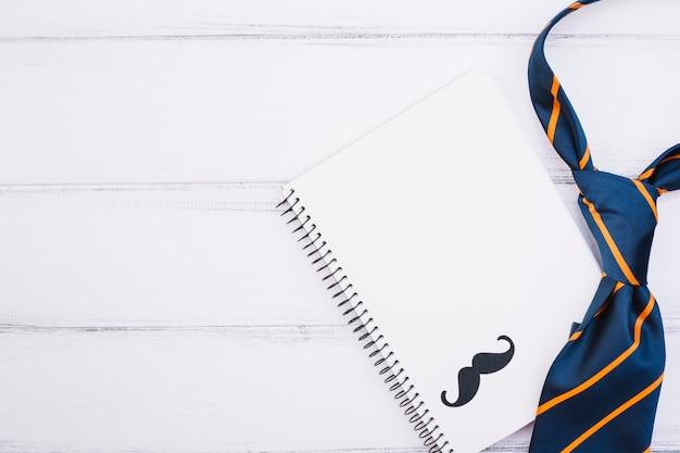 Cuaderno con bigote ornamental y corbata.
