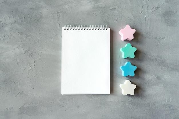 Cuaderno blanco abierto con estrellas sobre fondo gris de hormigón.