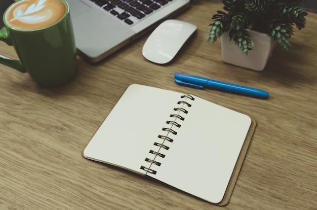 Cuaderno en blanco acostado sobre una mesa de madera y una taza de café verde en la computadora