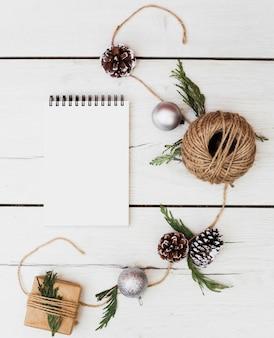 Cuaderno en blanco con adornos navideños alrededor