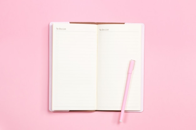 Cuaderno en blanco con bolígrafo encima de escritorio rosa pastel