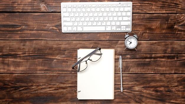Un cuaderno en blanco con un bolígrafo, gafas, un reloj despertador están en la parte superior de una mesa de oficina de madera