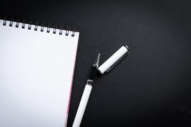 Cuaderno en blanco y bolígrafo sobre la mesa