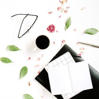 Cuaderno en blanco, capullo de rosa roja, vasos, hojas, café sobre superficie blanca