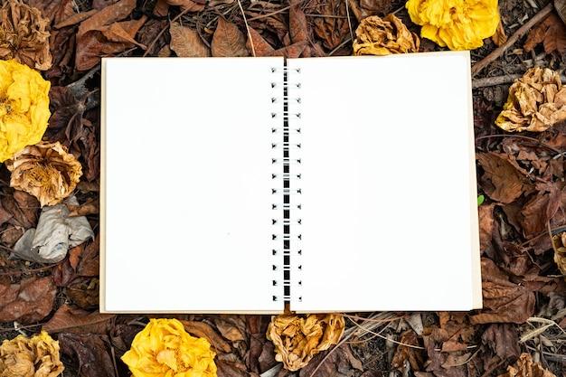 Un cuaderno en blanco colocado sobre una hoja amarilla, roja, naranja y flores secas de otoño en la vista superior de fondo de naturaleza otoñal