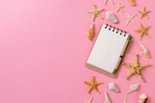 Cuaderno en blanco con concha para fondo rosa de vacaciones de verano, concepto de endecha plana vista superior.