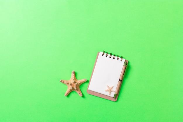 Cuaderno en blanco con concha para fondo verde de vacaciones de verano, concepto de endecha plana de vista superior.