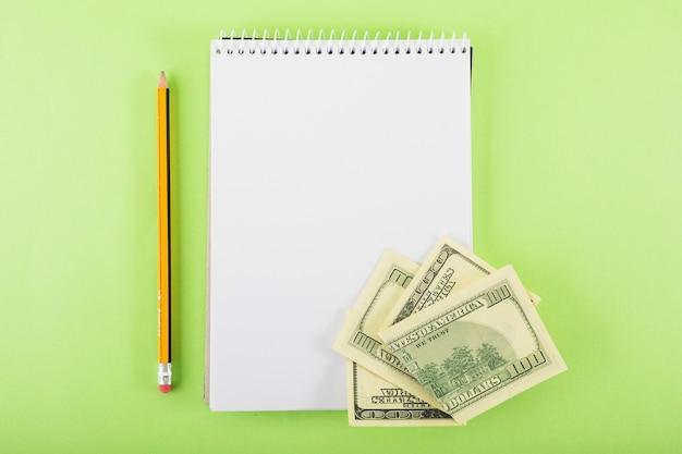 Cuaderno en blanco con dinero en la mesa
