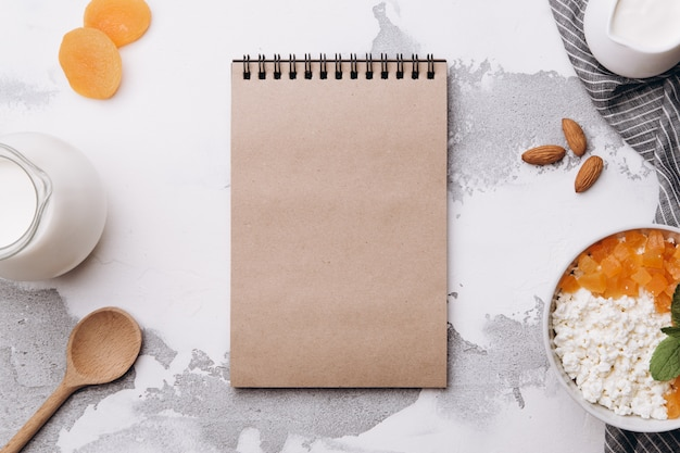 Cuaderno en blanco e ingredientes para el desayuno