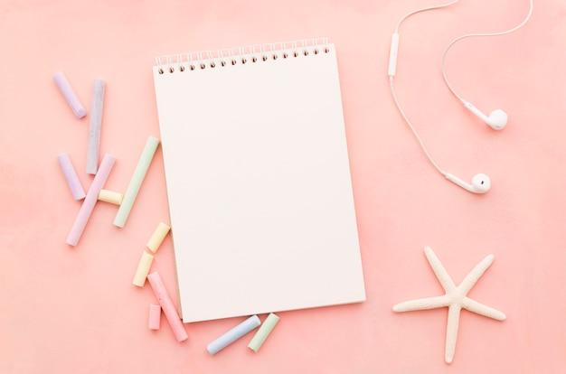 Cuaderno en blanco con estrella de mar y auriculares