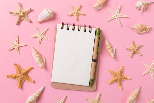 Cuaderno en blanco con estrellas de mar o conchas marinas sobre un fondo rosa, concepto de vacaciones de verano.