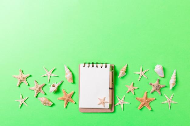 Cuaderno en blanco con estrellas de mar o conchas marinas sobre un fondo verde, concepto de vacaciones de verano.