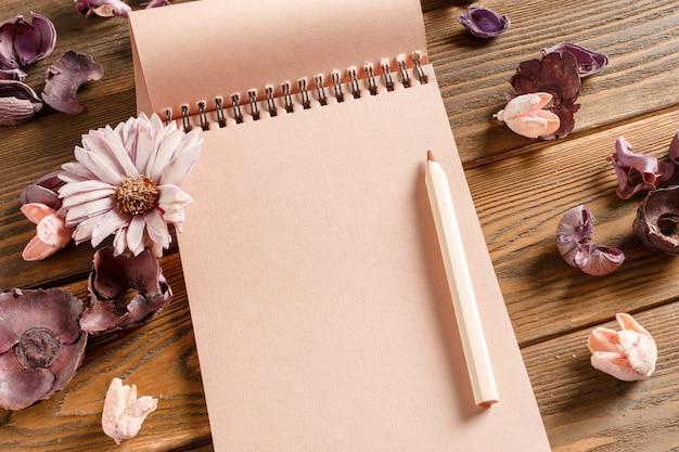 Cuaderno en blanco con flor en mesa de madera vintage