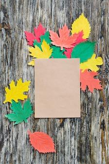 Cuaderno en blanco y hojas de papel de otoño en madera vintage
