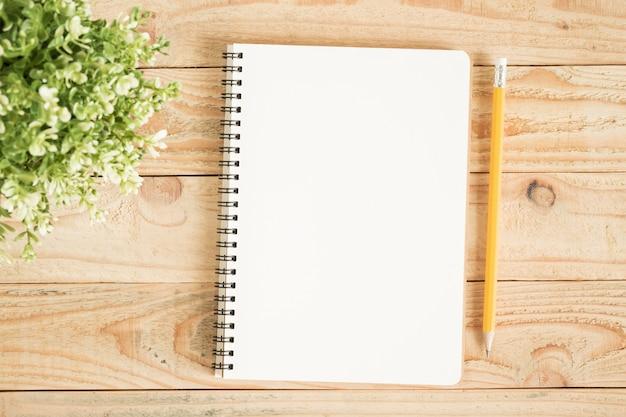 Cuaderno en blanco y lápiz amarillo en madera marrón