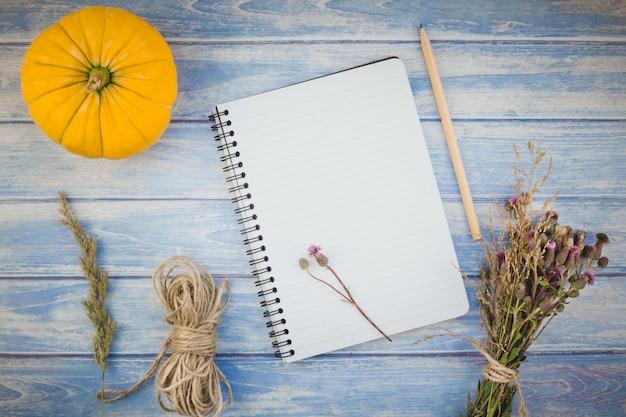 Cuaderno en blanco con lápiz y calabazas de otoño