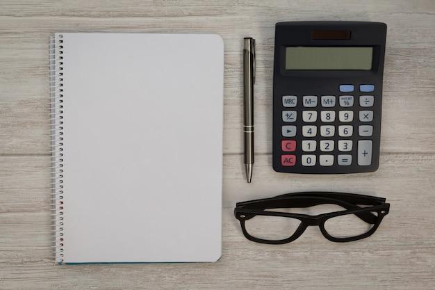 Un cuaderno en blanco con un lápiz y una calculadora.