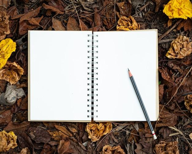 Un cuaderno en blanco y un lápiz colocados sobre una hoja amarilla, roja, naranja y flores secas de otoño en la vista superior de fondo de naturaleza otoñal