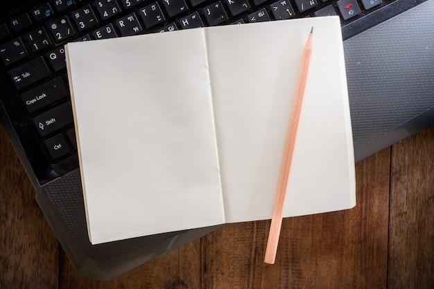 Cuaderno en blanco con lápiz en la computadora portátil