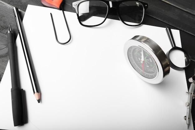 Cuaderno en blanco y lápiz con gafas en mesa de madera