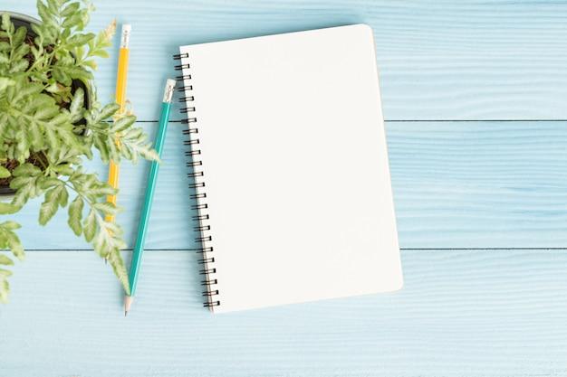 Cuaderno en blanco con y lápiz sobre fondo azul