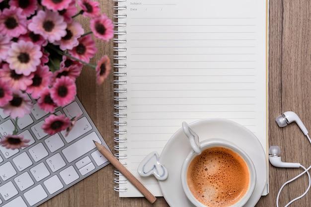 Cuaderno en blanco maqueta con taza de café y teclado de computadora blanco