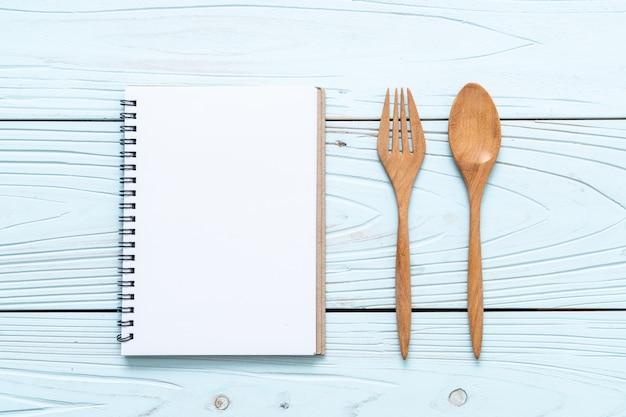 Cuaderno en blanco para nota de texto sobre superficie de madera con copia sapce