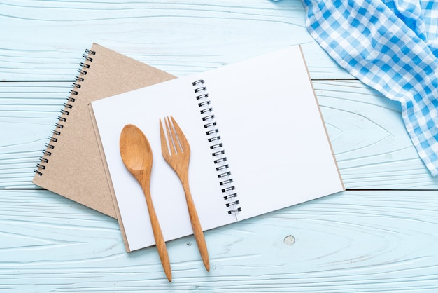 Cuaderno en blanco para nota de texto sobre superficie de madera