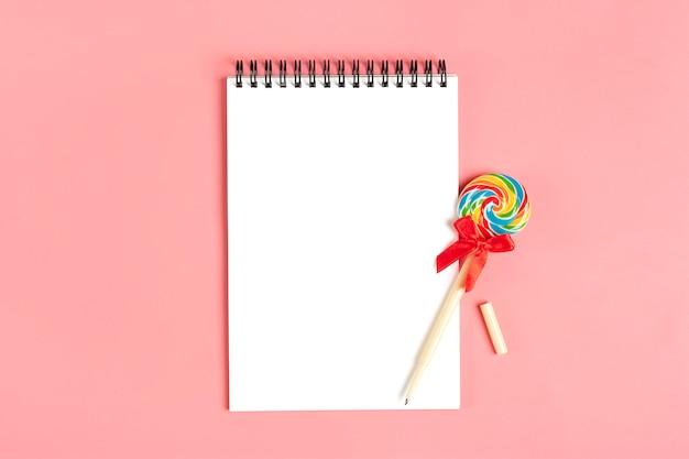 Cuaderno blanco para notas, bolígrafo - piruleta sobre fondo rosa endecha plana