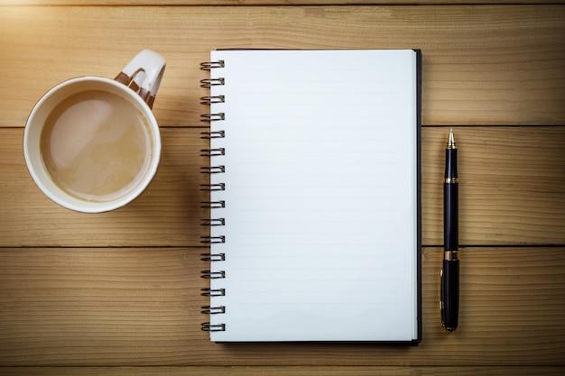 Cuaderno en blanco con las páginas en blanco en la tabla de madera, concepto del negocio.