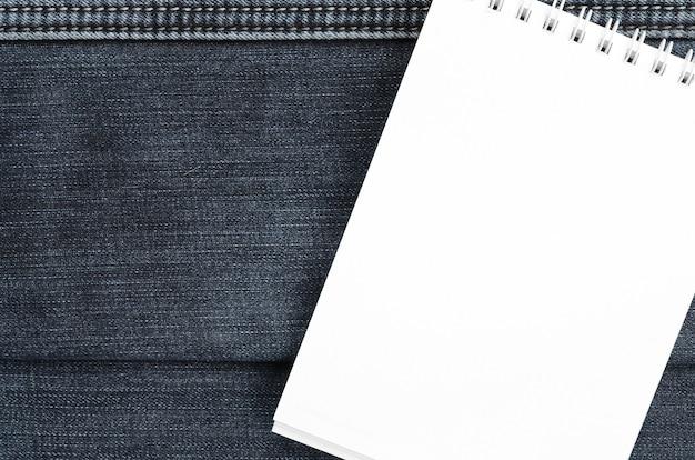 Cuaderno blanco con las páginas limpias que mienten en fondo azul marino de los vaqueros. imagen con espacio de copia.