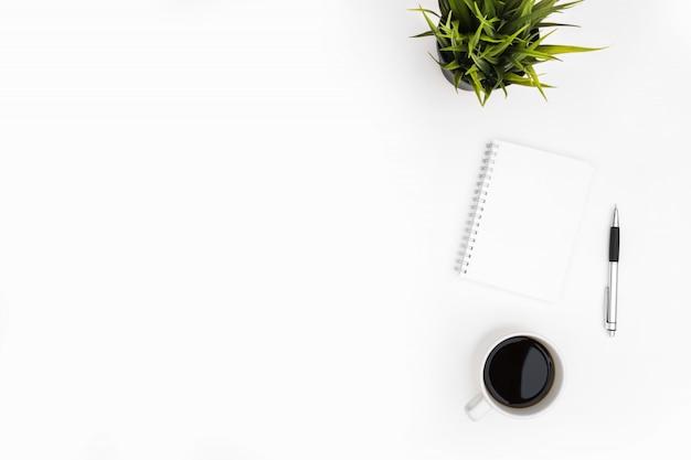 El cuaderno en blanco con la pluma está encima de la tabla blanca del escritorio de oficina con la taza de café. vista superior con espacio de copia, plano.