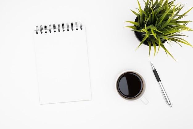 El cuaderno en blanco con la pluma está encima de la tabla blanca del escritorio de oficina con la taza de café.