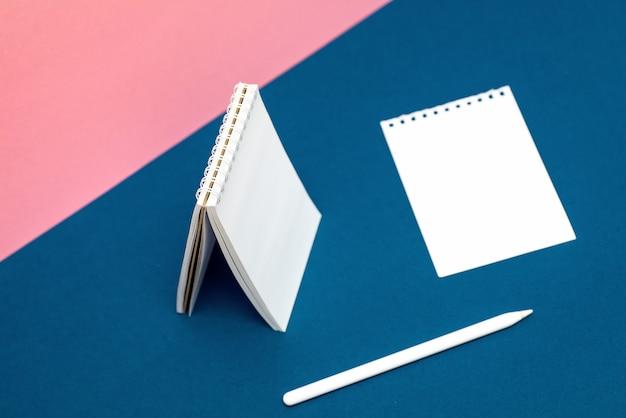 Cuaderno blanco, pluma y hoja sobre fondos multicolores.