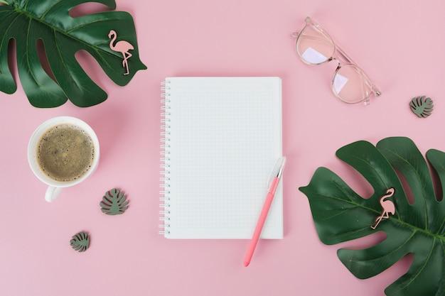 Cuaderno en blanco con la pluma en la mesa de color rosa
