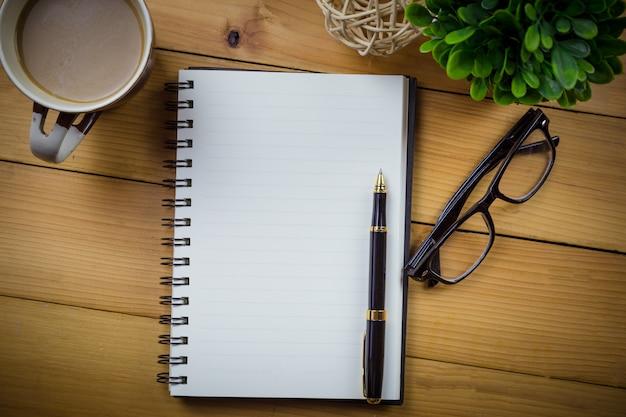 Cuaderno en blanco con la pluma y con los vidrios al lado de la taza de café en la tabla de madera