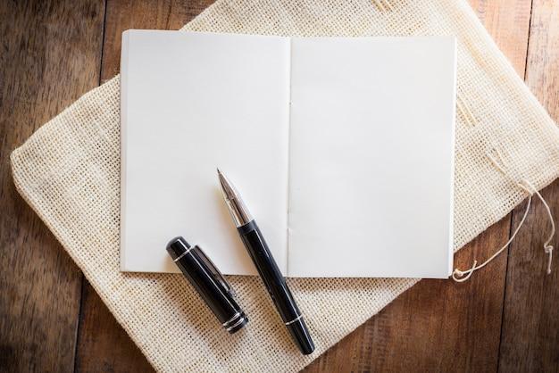Cuaderno en blanco con pluma