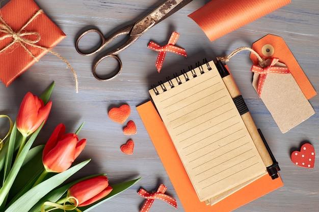 Cuaderno en blanco, regalo envuelto, materiales de envoltura y tulipanes anaranjados frescos en la mesa de madera