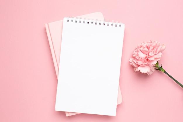 Cuaderno blanco y rosa con flor de clavel sobre un fondo rosa