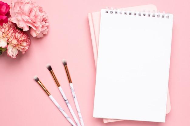 Cuaderno blanco y rosa con flores de clavel y pinceles de maquillaje sobre un fondo rosa