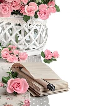 Cuaderno en blanco entre rosas rosadas hermosas, aislado en blanco. ¡feliz san valentin!